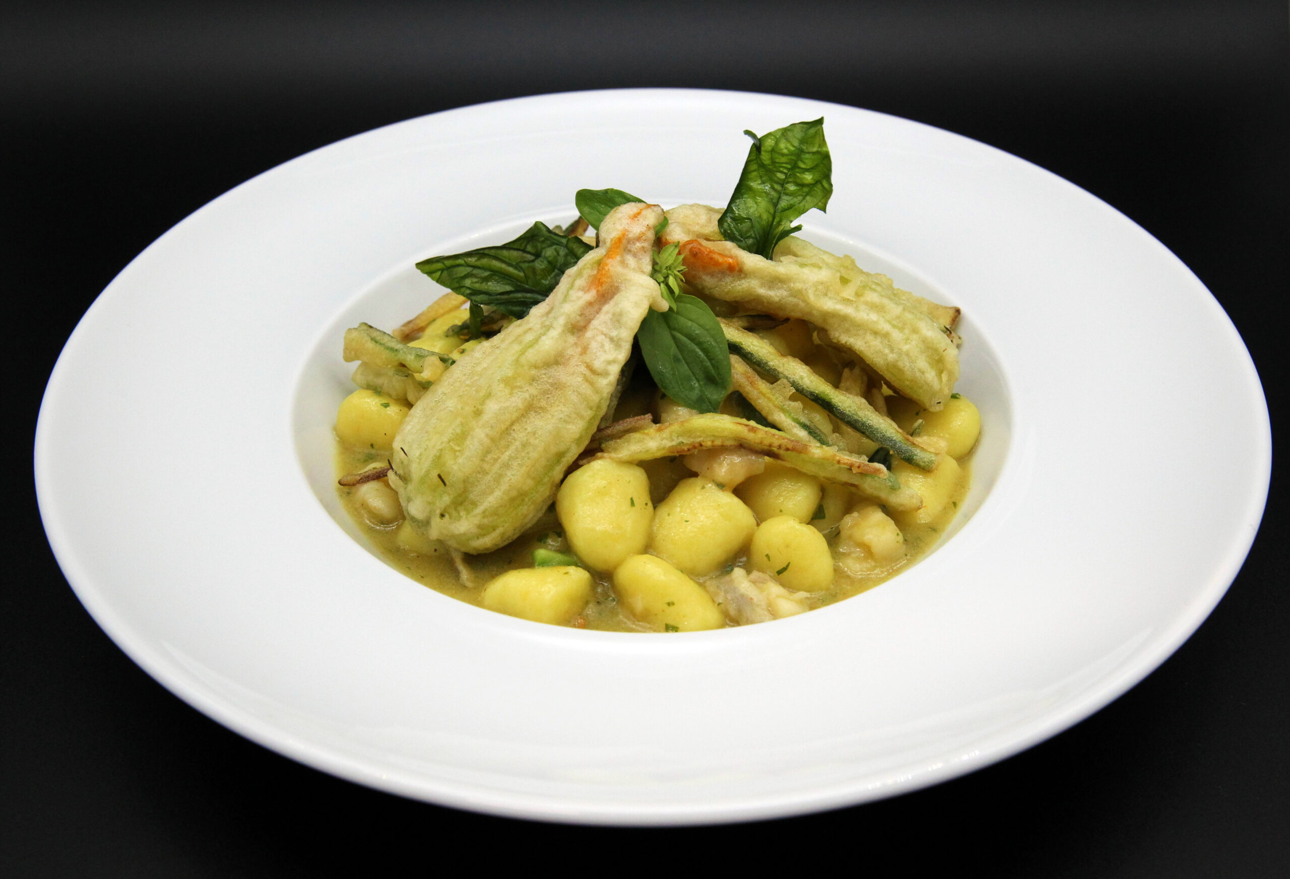Potato dumplings with monkfish ragout, courgette flowers and fennel powder